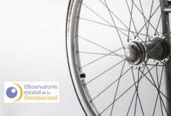 Imagen detalle de la rueda de una silla de ruedas y logo del OED