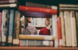 Imagen de dos estudiantes tras una pila de libros