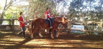 Un participante monta a caballo acompañado de dos monitoras durante una sesión de hipoterapia