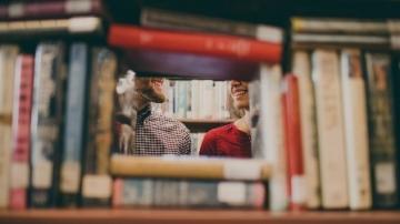 Fotografía de una pila de libros a través de la cual se ve parte de la cara de dos estudiantes
