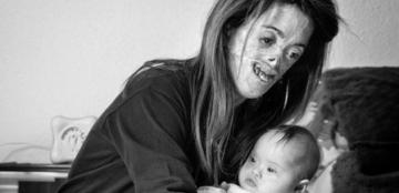 Fotografía 'Amor sin condición', de Vicente Guill Fuster, ganador del primer premio, en la que se ve a una mujer con discapacidad que sostiene en sus brazos a un bebé de pocos meses con síndrome de Down que descansa a